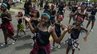 Members of Divaz dance group join participants in the Juneteenth Music Festival and parade on June 17, 2017 in Denver, Colorado. Organizers say that this is one of Denver's longest-running parades, dating back to the 1950s.
