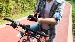 Woman riding bike wearing smartwatch