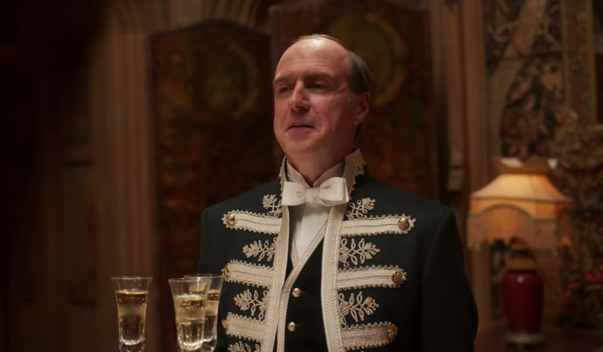 Downton Abbey Molesley stands with a tray of champagne to serve the royals