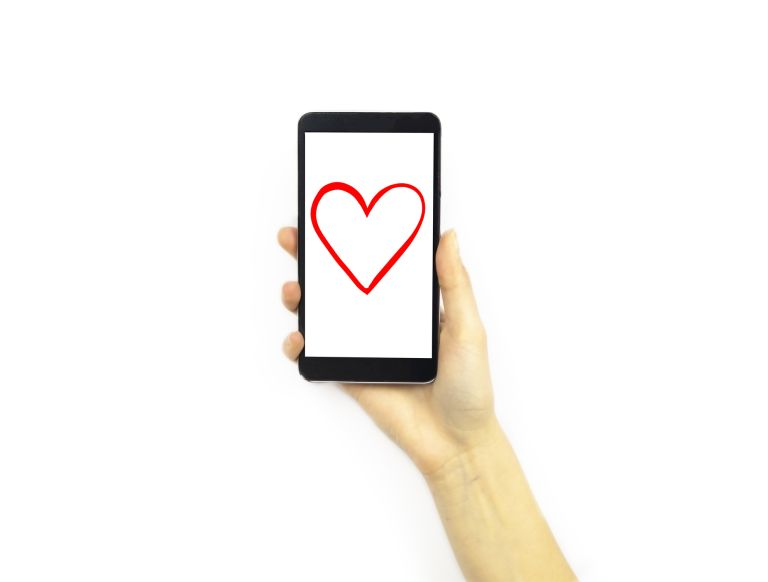 Mobile phone with a heart on the screen being held by a hand