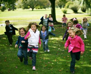 A group of children runs in a park.