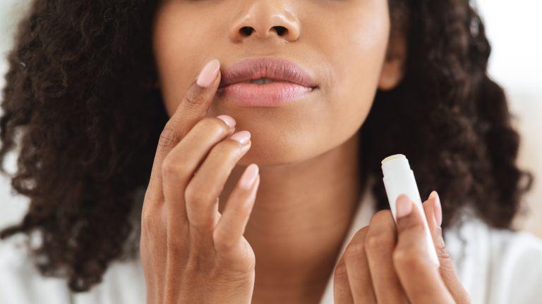 Woman putting on lip balm