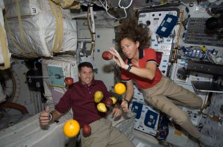 Astronauts Shane Kimbrough and Sandra Magnus Floating with Fruit