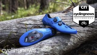 Best road shoes: a pair of blue Shimano S-phyre shoes resting on a log