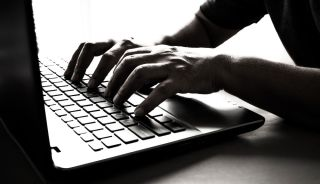 Hands type on a laptop keyboard.