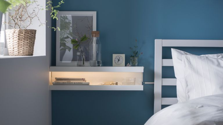 DIY bedside table: Ikea shelves used as a bedside table with integrated light in a modern bedroom with blue walls