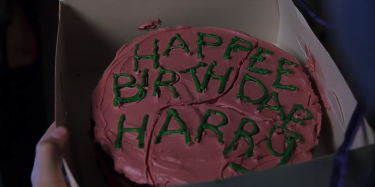 Harry Potter holds a birthday cake, which reads 'Happee Birthdae Harry' in a scene from Harry Potter and the Sorcerer's Stone