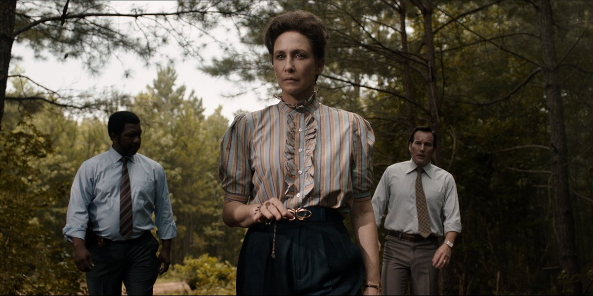 Vera Farmiga as Lorraine Warren with Patrick Wilson as Ed Warren and a police officer in the woods in THe Conjuring The Devil Made ME Do it