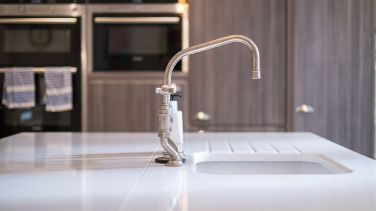 Kitchen sink and silver tap in front of cabinet