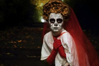 Woman in Day of the Dead or Halloween face paint.