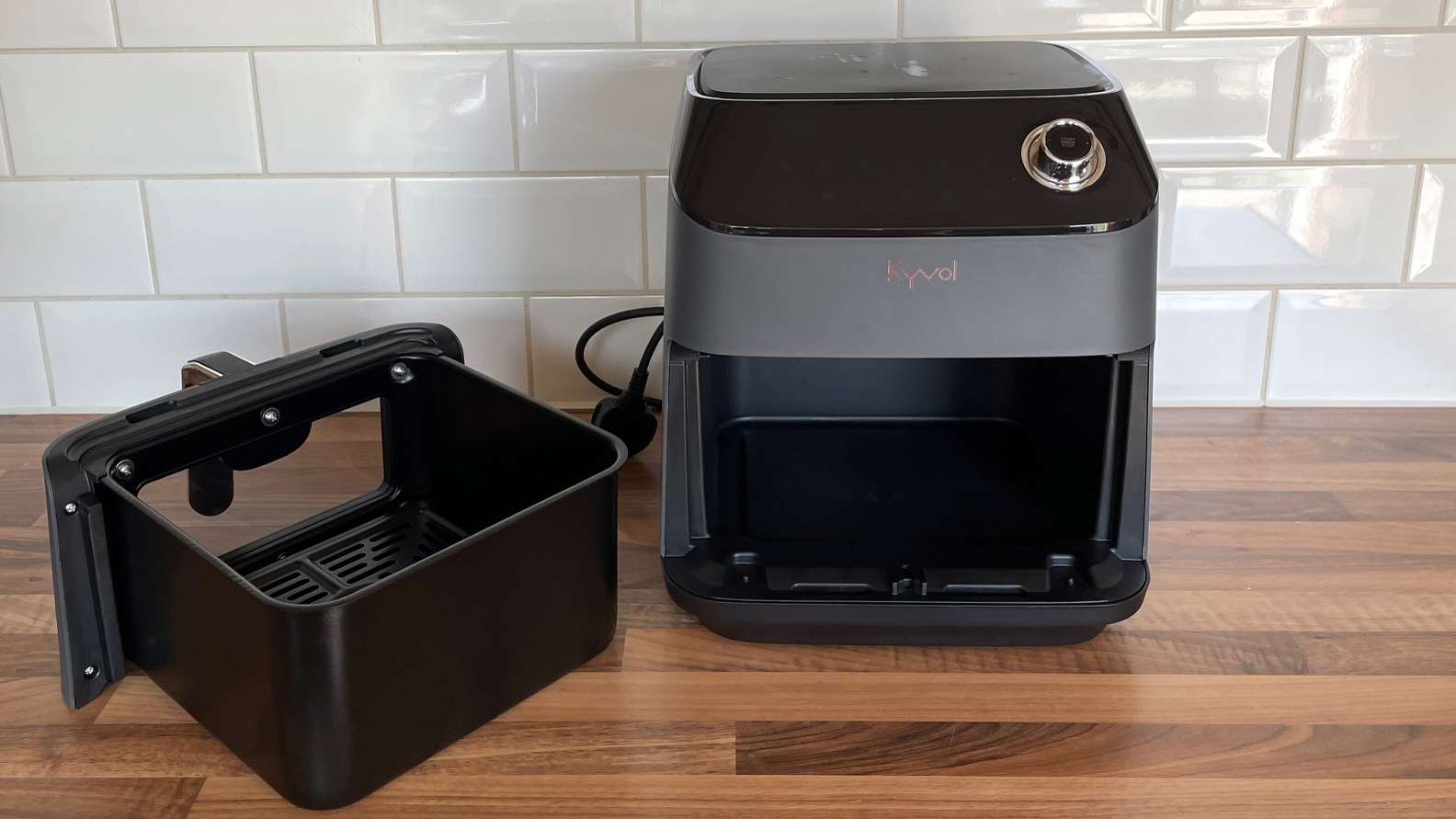 The Kyvol AF600 Air Fryer on a kitchen countertop with the frying basket removed and positioned to the left hand-side