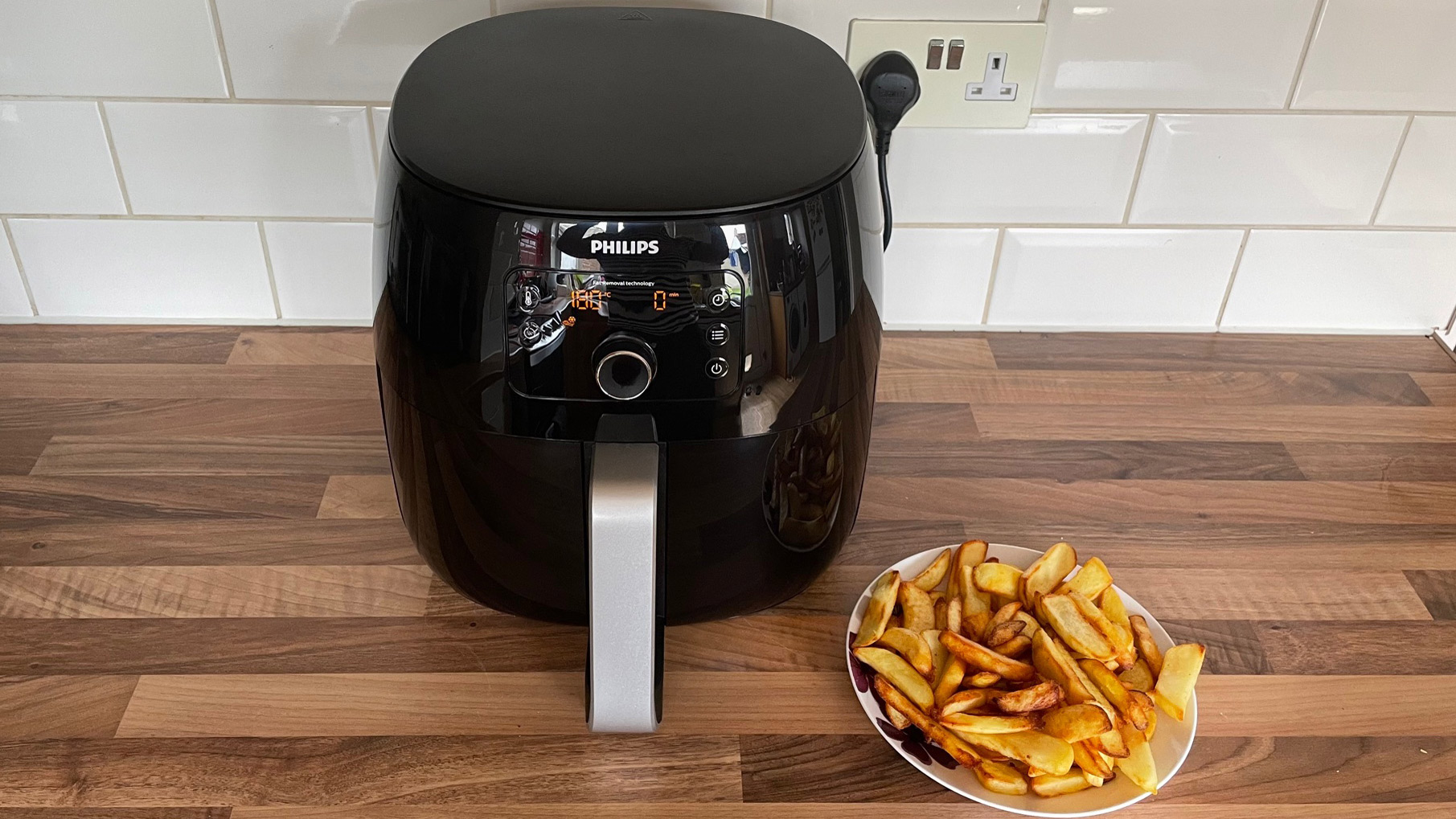 Philips Airfryer XXL HD9650/99 next to a plate of chips that were cooked in the air fryer
