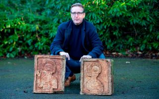 Dutch art detective Arthur Brand poses with two limestone Visigoth reliefs from the seventh century in London on Jan. 20, 2019.