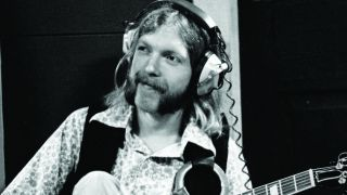 Duane Allman in the studio, wearing headphones, a flower-patterened shirt and waistcoat and holding a guitar.