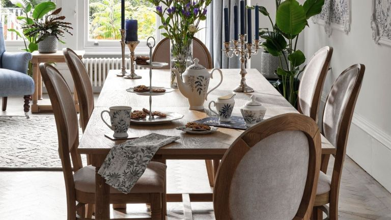 Laura Ashley / Next dining room set with oak upholstered chairs, oak table, floral centerpiece and light colored curtains