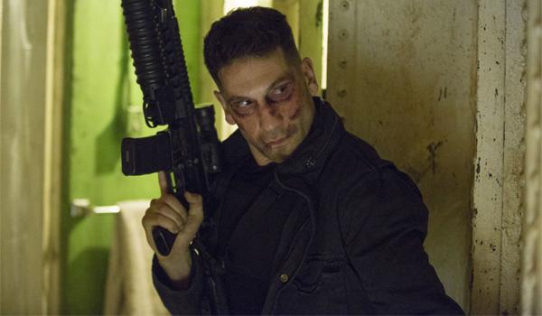 jon bernthal with large gun sneaking around corner as Punisher