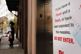 A sign in Brooklyn, New York, where there is currently a measles outbreak, warns people not to enter a building if they have symptoms of the disease.