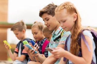 Happy elementary school students with smartphones and backpacks sitting on bench outdoors texting.