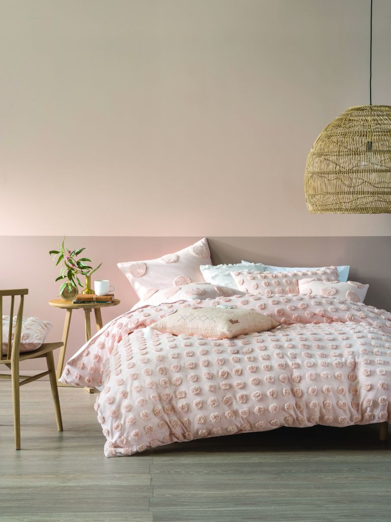 Pink bedroom with pom pom bedding and pink colour block walls