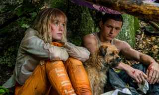 Still shot from Chaos Walking with Tom Holland and Daisy Ridley sitting together.