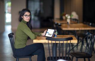 eine junge Frau sitzt in einem Cafe und nimmt an einem Onlinemeeting teil
