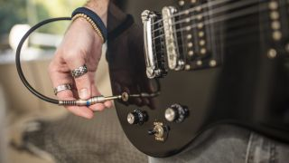 Man plugs guitar cable into his guitar