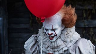 Bill Skarsgard as Pennywise holding red balloon in IT movie