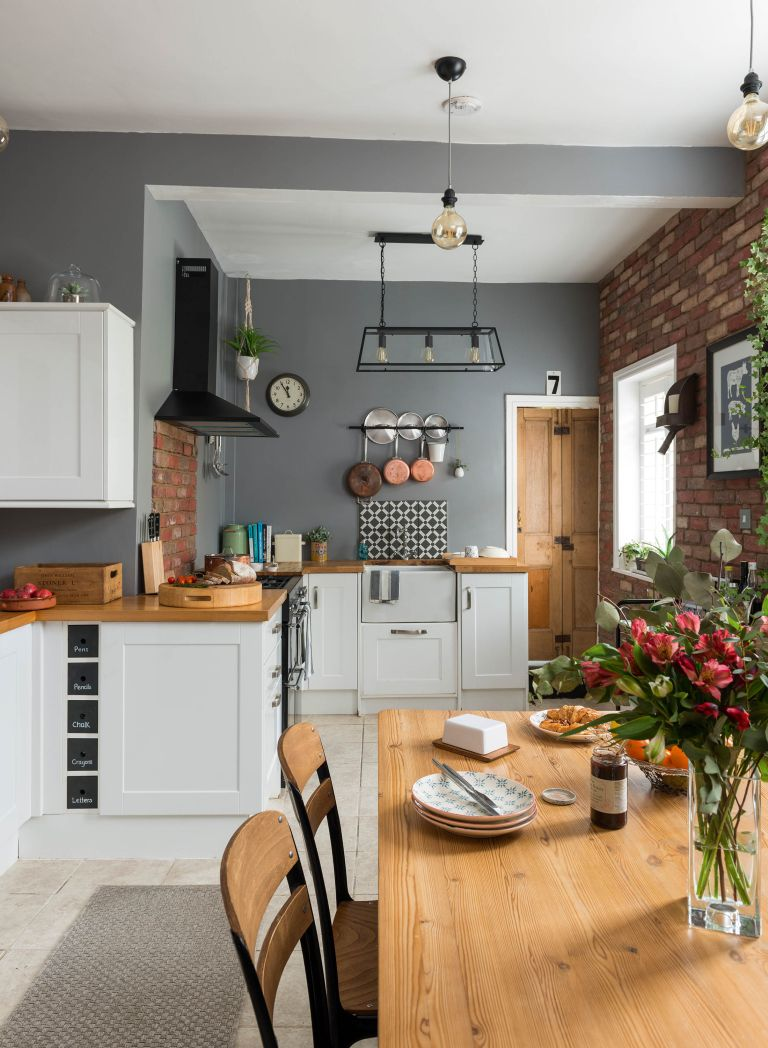 shaker style kitchen with grey walls, a wooden dining table, wooden worktops and industrial pendant lights