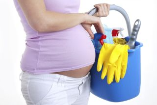 A pregnant woman holds a bucket of cleaning supplies