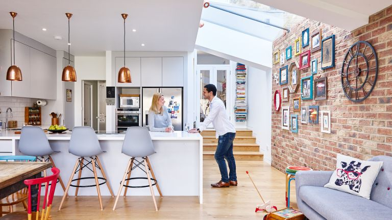 couple in their modern open plan kitchen diner with exposed brick wall