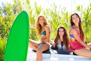 Surfer girls holding surfboards in a convertible car.