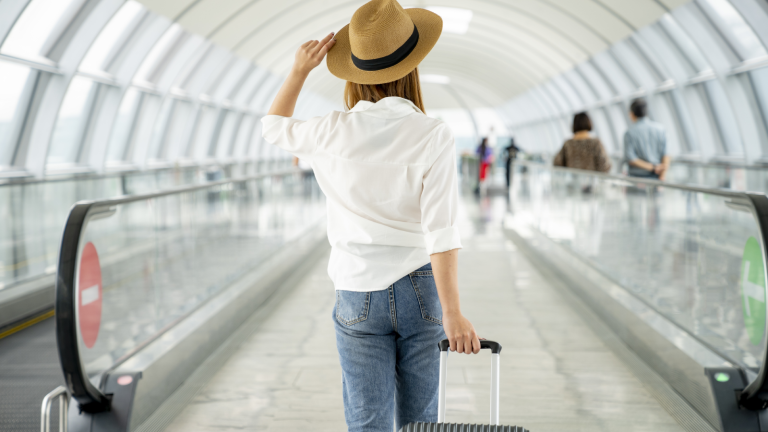Cyber Monday travel deals - woman with suitcase at airport
