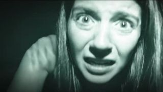 Emily Bader looks into the camera frightened in Paranormal Activity: Next of Kin.