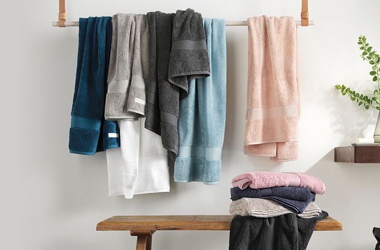 Learn how to wash towels with this easy guide: Towels on towel rail hung up in a bathroom for a feature on how to wash towels