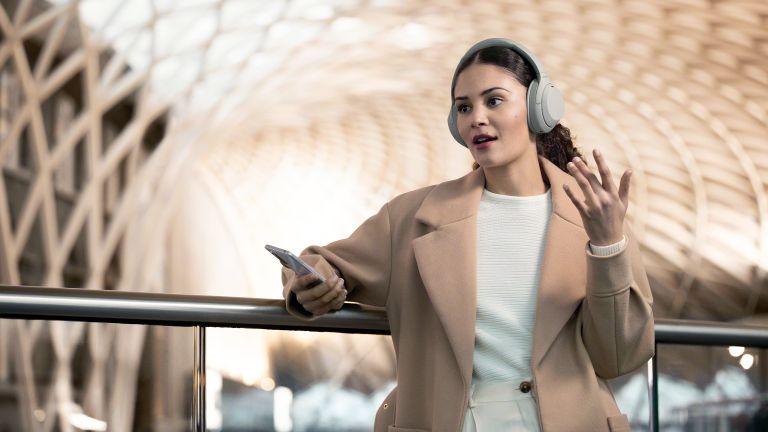 Best wireless headphones 2021, woman wearing wireless headphones and holding phone