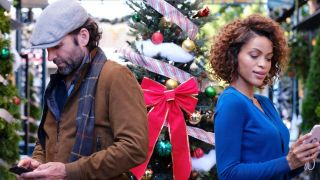 A woman and a man stand in front of many christmas trees looking at their phones and not realizing they're texting each other!