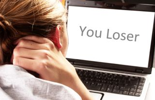 "A girl looks at a computer screen that says ""You Loser."""