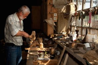 An older man works with wood