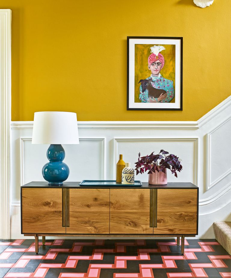 A modern hallway idea with yellow walls, white woodwork and a wooden mid-century modern sideboard