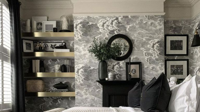gold shelving in bedroom with grey wallpaper