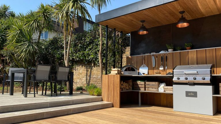 how to design an outdoor kitchen: covered kitchen space with modern patio and dining area