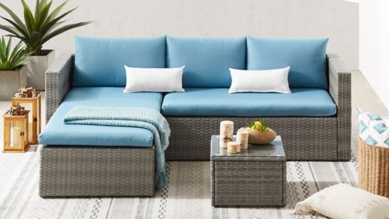 A rattan corner sofa with chaise lounger and blue cushions on a patio terrace