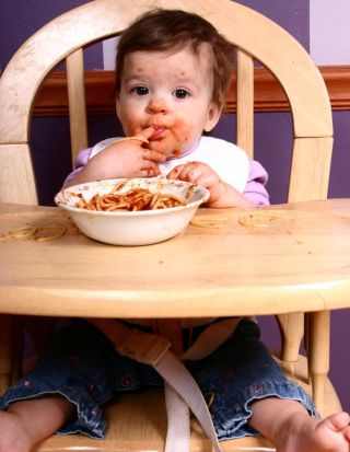 messy baby eating in high chair with spaghetti all over her face.