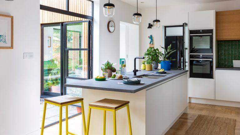 white kitchen diner with yellow bar stools and Crittall style doors