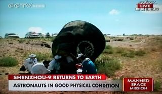This photograph of a China CCTV broadcast shows the Shenzhou 9 space capsule lying on its side after landing in an autonomous region of China in Inner Mongolia on June 29, 2012 Beijing time (10 p.m. June 28 EDT) to end a 13-day mission to the Tiangong 1 s