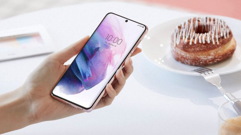 Samsung Galaxy S22 being held by a woman next to a plate with a donut on it