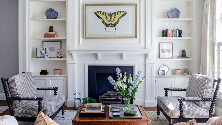 A white living room with built-in alcove shelves either side of a fireplace with two gray armchairs.
