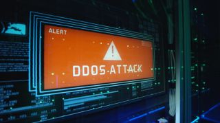 The words 'DDoS Attack' displayed in an orange box on a monitor embedded in a series of rack-mounted servers.