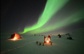 Auroras Glow Over Skywatchers in Swedish Mountains by Chad Blakley