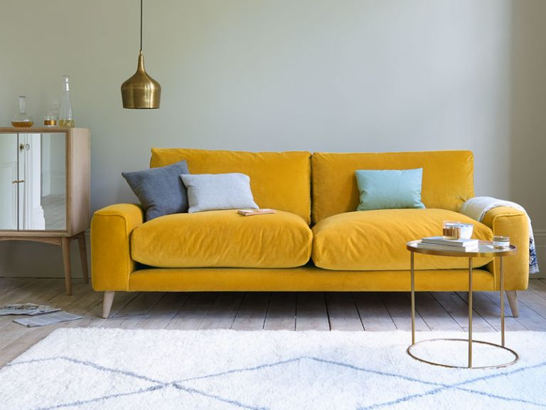 living room with yellow velvet sofa by loaf